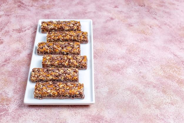 Gezonde delicios mueslirepen met chocolade, mueslirepen met noten en droge vruchten, bovenaanzicht Premium Foto