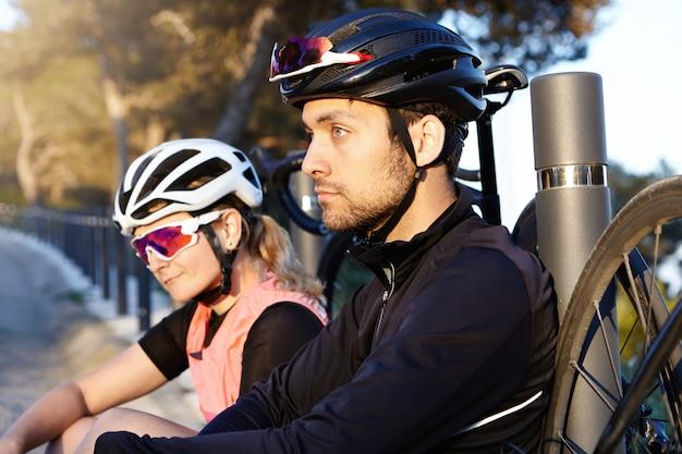 Gezonde en actieve levensstijl. twee fietsreizigers rusten op de brug in de ochtend na een lange rit, selectieve focus op knappe en charismatische jonge bebaarde man met positieve doordachte gezichtsuitdrukking Gratis Foto