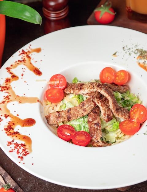 Gezonde gegrilde rundvlees caesar salade met kaas, cherry tomaten en sla Gratis Foto