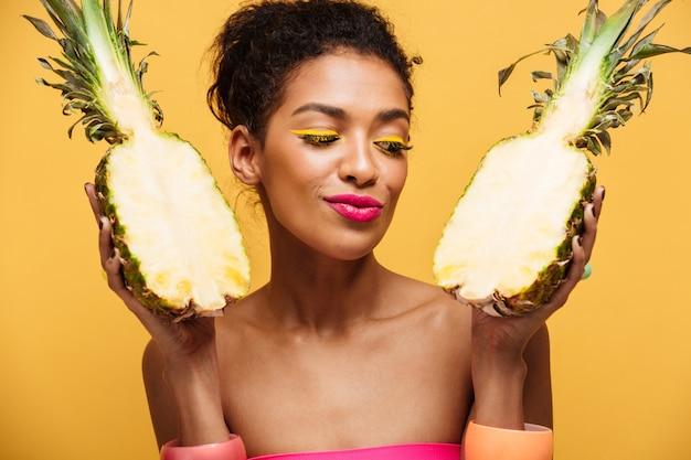 Gezonde gemengd rasvrouw met maniermake-up die detox hebben die verse rijpe ananas houden die in half geïsoleerd, over gele muur wordt verdeeld Gratis Foto