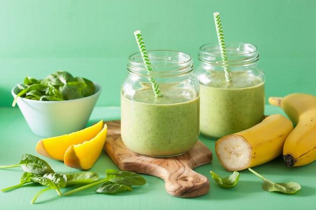 Gezonde groene smoothie met spinazie mangobanaan in glazen potten Premium Foto