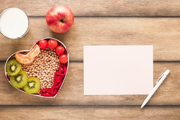 Gezonde groenten; vruchten; melk met blanco papier en pen op houten tafel Gratis Foto