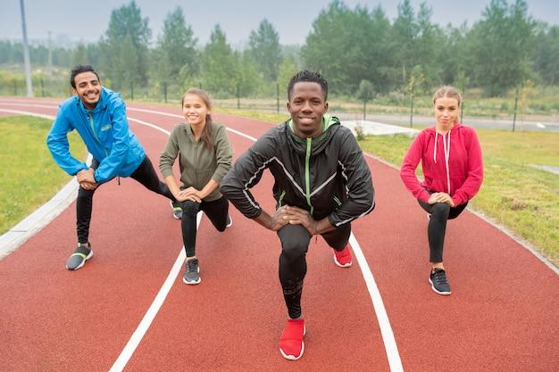 Gezonde jonge interculturele vrienden in activewear die tijdens training op renbanen van openluchtstadion uitoefenen Premium Foto