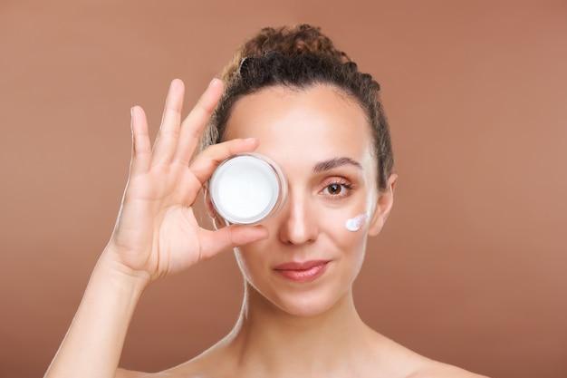 Gezonde jonge mooie vrouw met een klein potje verjongende gezichtscrème met het oog terwijl ze geïsoleerd voor de camera staat Premium Foto