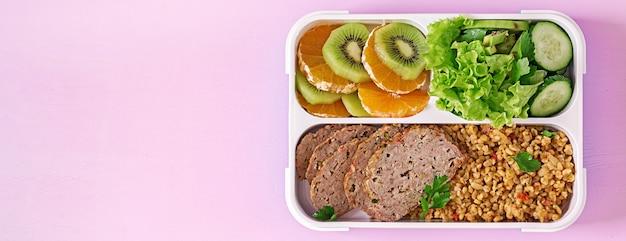 Gezonde lunch met bulgur, vlees en verse groenten en fruit op een roze tafel. fitness en gezonde levensstijl concept. lunchbox. bovenaanzicht Premium Foto
