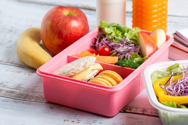 Gezonde lunchdoos set sandwichkaas met cracker en salade in doos, banaan en appel, jus d'orange en melk. Premium Foto