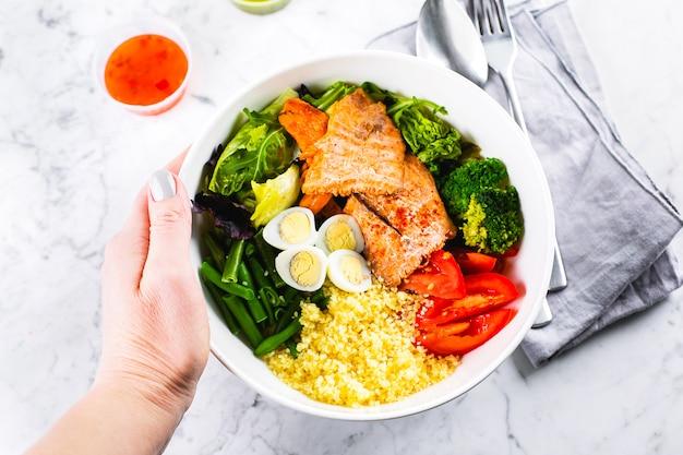 Gezonde maaltijd, keto food concept. vissalade kom op marmeren tafel. salade met zalm, couscous, groenten, kwarteleitjes. bovenaanzicht, kopieer ruimte Premium Foto