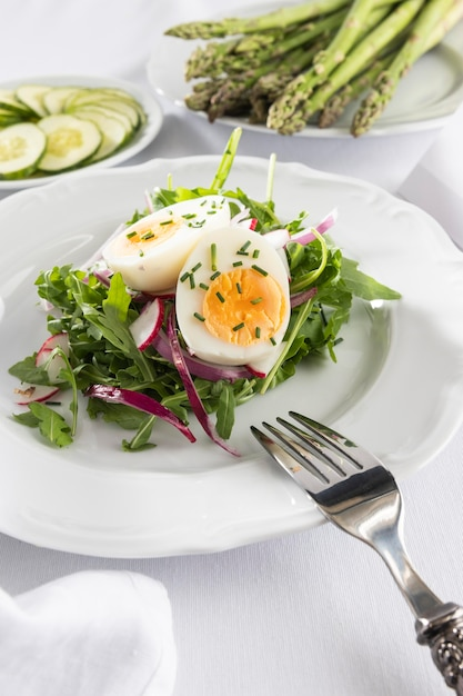 Gezonde salade met ei op een witte plaat-samenstelling Gratis Foto