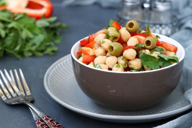Gezonde salade van kikkererwten, groene olijven, peper en peterselie, op donker Premium Foto