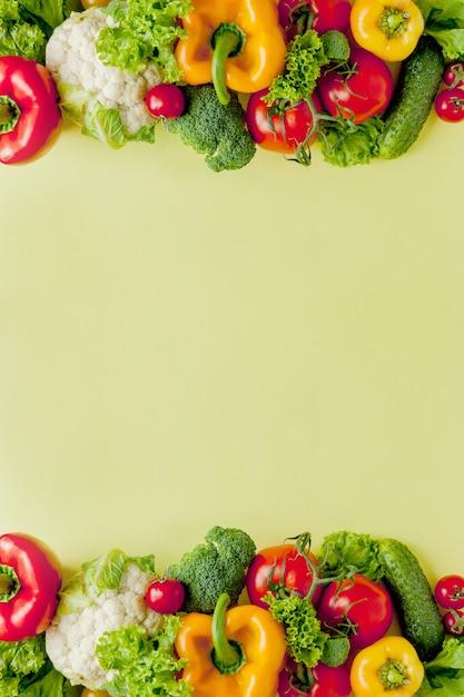 Gezonde schone eetlay-out, vegetarisch voedsel en dieetvoedingsconcept. diverse verse groenteningrediënten voor salade op gele lijstachtergrond, hoogste mening, kader, banner. Premium Foto