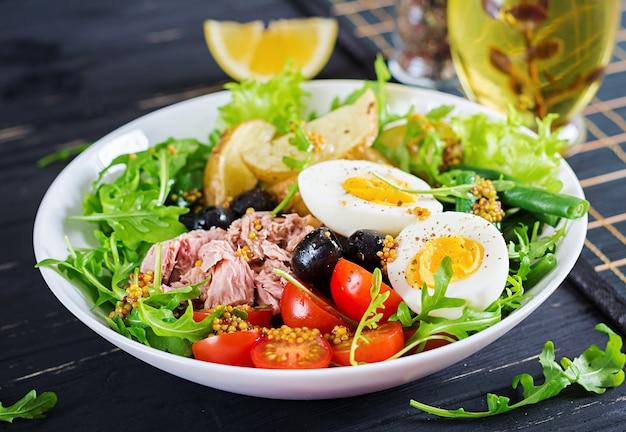 Gezonde stevige salade van tonijn, sperziebonen, tomaten, eieren, aardappelen, zwarte olijven close-up in een kom op tafel Gratis Foto