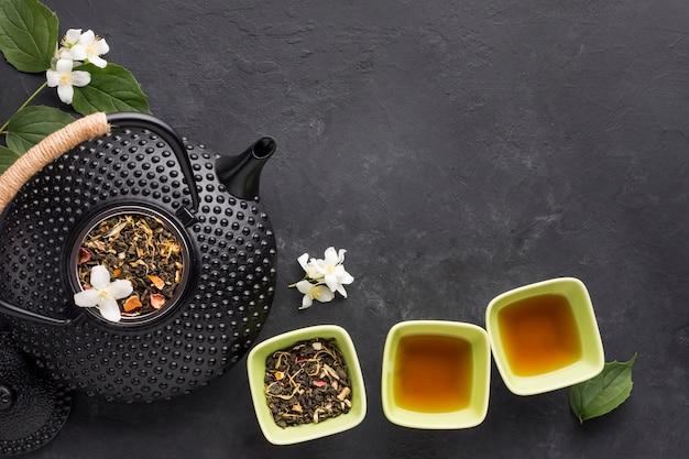 Gezonde thee met aromatische droge thee in kommen en theepot op zwarte ondergrond Gratis Foto