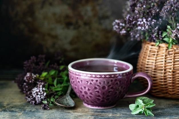 Gezonde thee van oregano bloemen in een mooie mok op een houten achtergrond. kopieer ruimte Gratis Foto