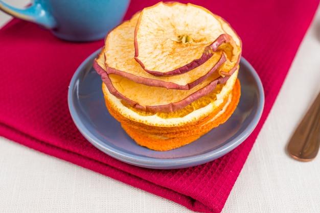 Gezonde voeding biologische voeding. gesneden en gedroogde appel, sinaasappel en kopje thee op textiel tafelkleed. Premium Foto