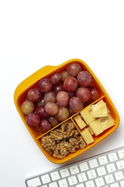 Gezonde voeding in plastic bakjes klaar om te eten met kaas, druiven en walnoten op de werktafel. Premium Foto