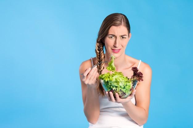 Gezonde voeding - jonge vrouw met salade Premium Foto