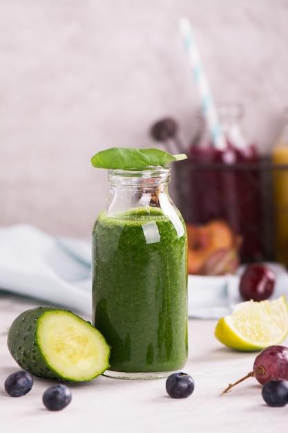 Gezonde zoete groene smoothie in een kleine glazen fles Premium Foto