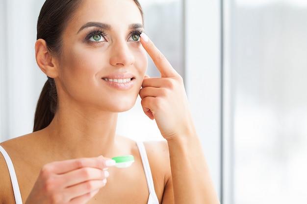 Gezondheid. jong meisje houdt contactlens in handen. portret van een mooie vrouw met groene ogen en contactlenzen. gezonde uitstraling. hoge resolutie Premium Foto