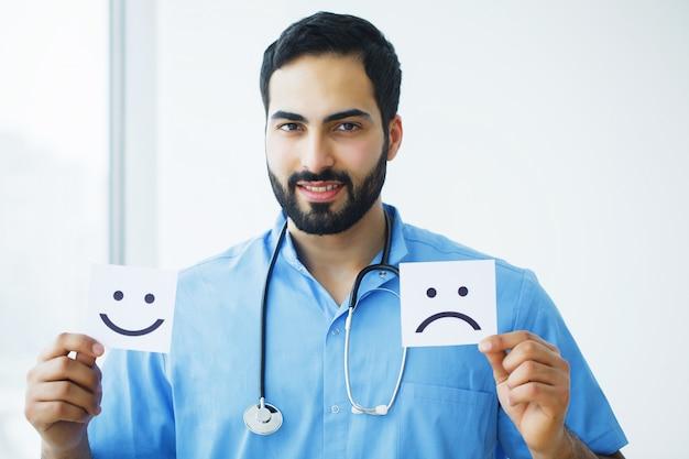 Gezondheidszorg. arts holding kaarten met symboolpret en droevige glimlach, medisch concept Premium Foto