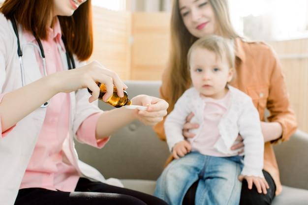 Gezondheidszorg en geneeskunde concept. vrouw hand gieten medicatie of antipyretische siroop van fles tot lepel. weinig babymeisje en mooie moederzitting op de bank op de achtergrond Premium Foto