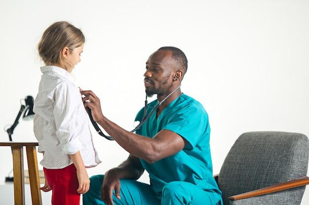 Gezondheidszorg en medisch concept - arts die met stethoscoop aan kindborst luisteren in het ziekenhuis Gratis Foto
