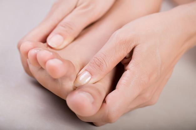 Gezondheidszorg en medisch concept. vrouw masseert haar pijnlijke voet Premium Foto
