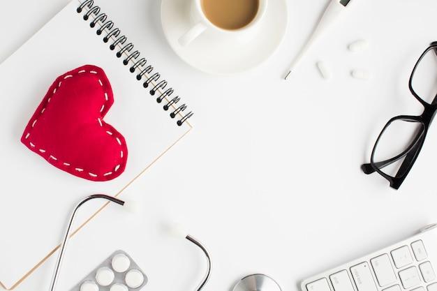 Gezondheidszorgtoebehoren met rood stuk speelgoed hart en spiraalvormige blocnote op witte achtergrond Gratis Foto