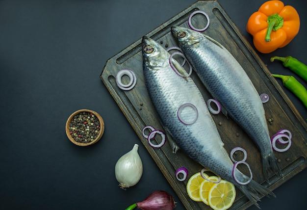 Gezouten haring met uien en kruiden op een snijplank Premium Foto