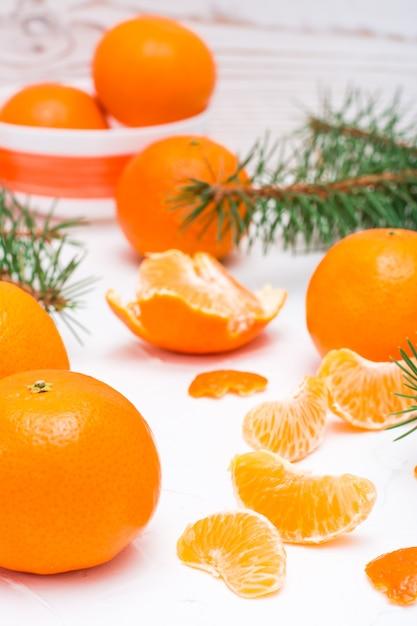 Gezuiverde mandarijn plakjes, hele mandarijnen en dennentakken op een witte tafel Premium Foto