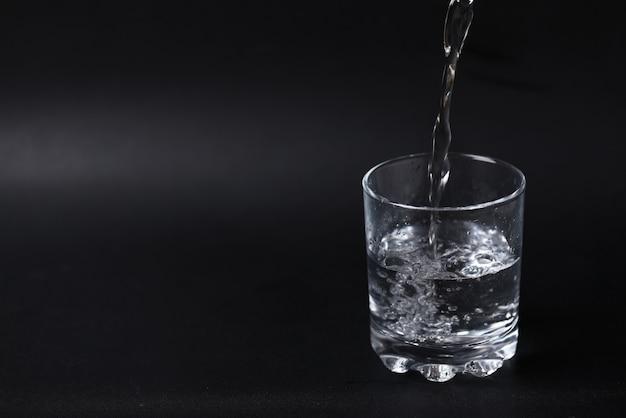 Giet water in een half gevuld glas. Gratis Foto