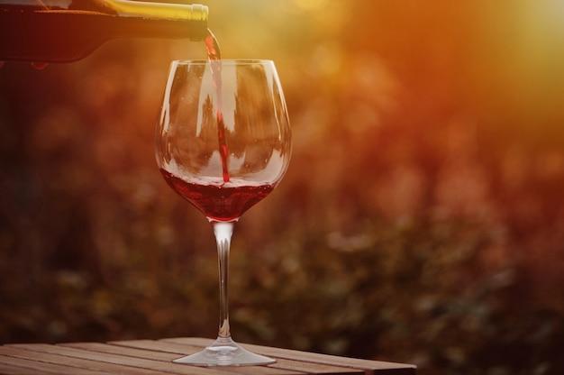 Gieten rode wijn in het glas. Premium Foto