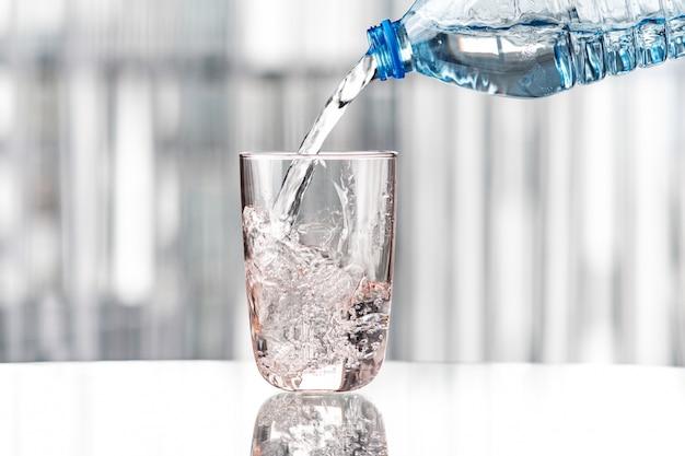 Gieten van water uit blauwe fles in glas Premium Foto