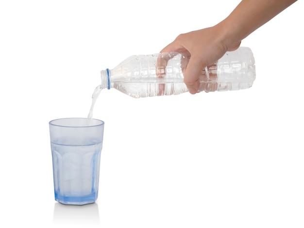 Gietend water van plastic fles in glas dat op wit wordt geïsoleerd. uitknippad Premium Foto