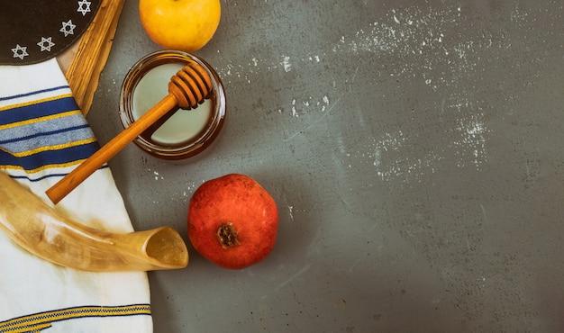 Gietende honing op appel en granaatappel met honingssymbolen van joods nieuwjaar, rosh hashanah. Premium Foto