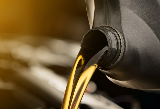 Gietende olie smeermiddel motor auto van zwarte fles op geïsoleerde witte achtergrond Premium Foto