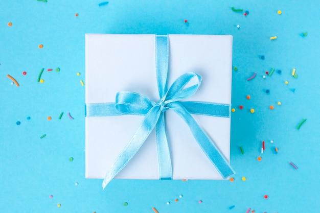 Gift, kleine doos vastgebonden met een satijnen blauwe lint. geschenk concept. Premium Foto