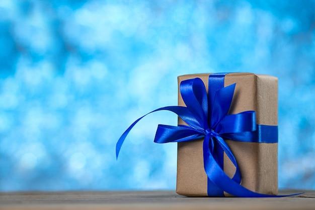 Giftdoos met een lintboog op het bureau op blauw Premium Foto