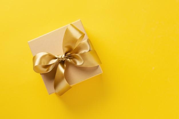 Giftdoos met gouden lint op heldere achtergrond Gratis Foto
