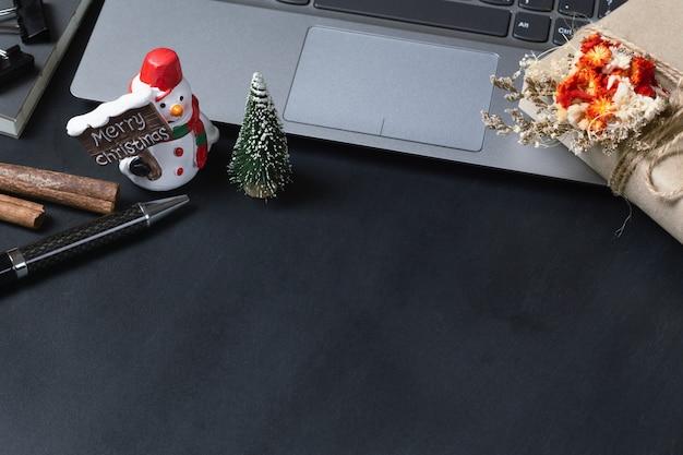 Giftdoos op laptop en sneeuwmanstuk speelgoed Premium Foto