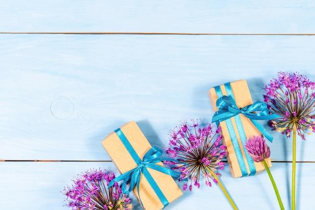 Giften op een blauwe houten achtergrond met paarse bloemen. Premium Foto