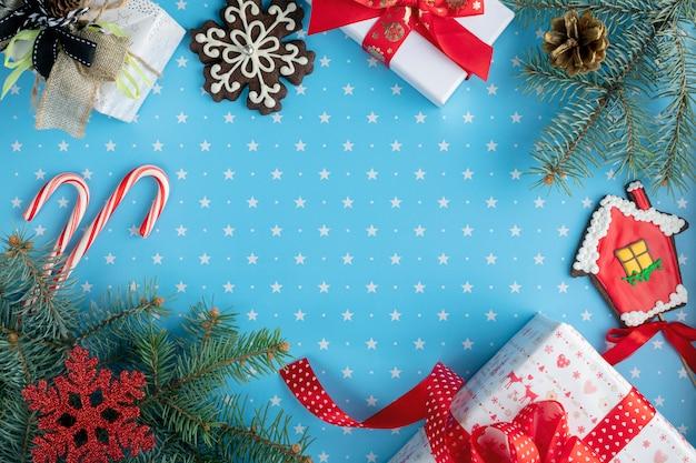 Giften, sparrentakken met dennenappel, sneeuwvlokpeperkoek, huispeperkoek, snoepjes en snuisterijen op blauwe achtergrond met patroon van sterren ... kerstmis, winter, nieuw jaarconcept. bovenaanzicht Premium Foto