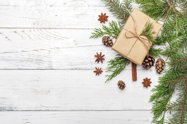 Giften voor nieuw jaar die in ambachtdocument dichtbij nette takken en kegels worden verpakt op witte houten hoogste mening als achtergrond copyspace Premium Foto