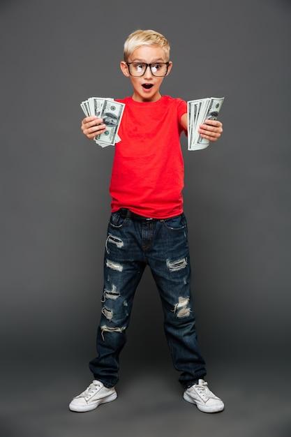 Gillend verrast weinig jongenskind dat geld toont. Gratis Foto
