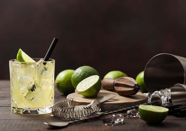 Gimlet kamikaze-cocktail in kristalglas met limoenplak en ijs op houten oppervlak met verse limoenen en zeef met shaker. Premium Foto