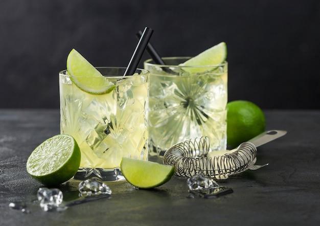 Gimlet kamikaze-cocktail in kristallen glazen met limoenplak en ijs op zwarte ondergrond met verse limoenen en zeef. Premium Foto