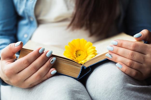 Girl's handen op een boek met een gele bloem Premium Foto