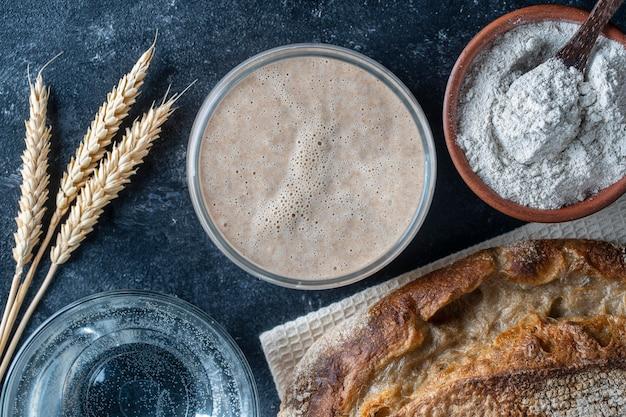 Gistvrij zuurdesembrood, bloem, water en glazen pot met gistdeeg op tafel. gistdeeg voorbereiden voor brood, broodjes, gebak of pizza, close-up, bovenaanzicht. kookproces Premium Foto