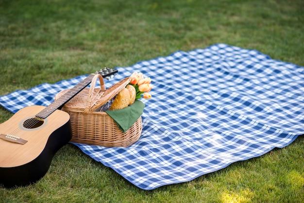 Gitaar en een picknickmand op een deken Gratis Foto