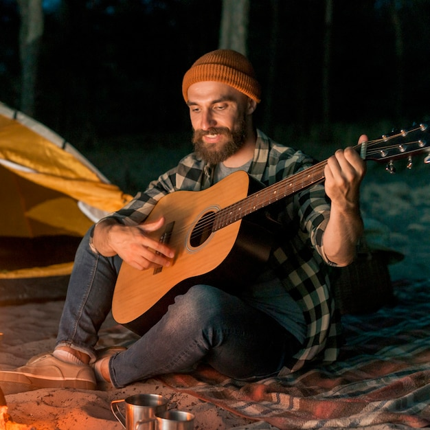 Gitarist die kampeert en zingt door een vreugdevuur Gratis Foto