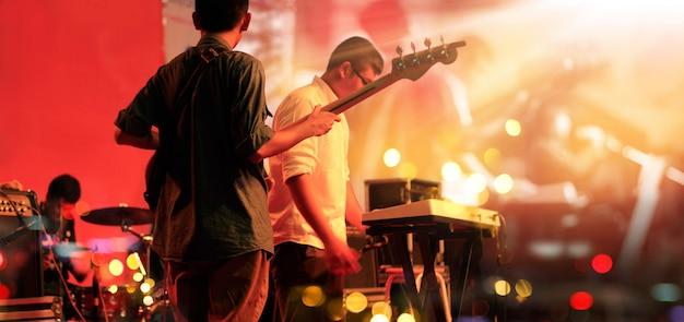 Gitarist en band op stadium voor achtergrond. Premium Foto